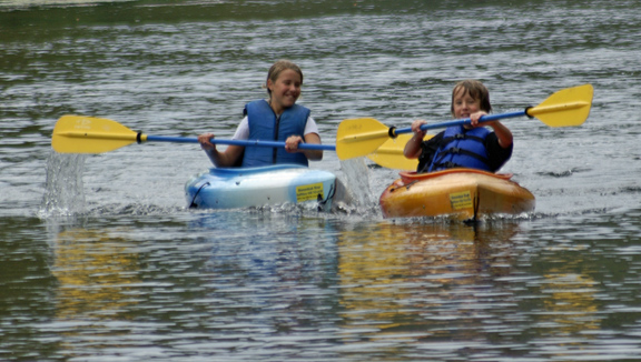 Kids loving kayaking river